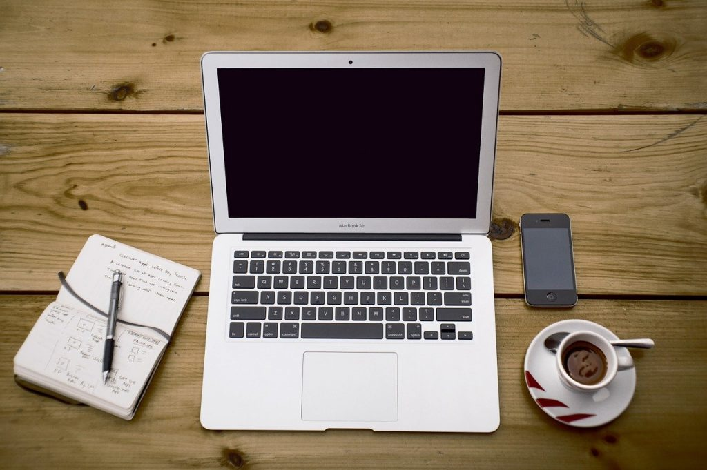 Picture of open laptop on a table with a cup of coffee and a pad of paper, a pen and a cellphone.